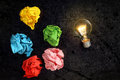 Inspiration lit lightbulb with crumpled paper balls idea or concept Royalty Free Stock Images