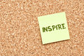 Inspire on cork board with note paper yellow sticky Royalty Free Stock Photo