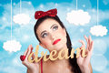 Inspire to create pinup your dreams to the sky attractive young girl looking up clouds of inspiration with words dream in hand Stock Photo