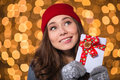 Inspired lovely girl holding blank cards with red ribbon in hat and knitted mittens over glittering background Royalty Free Stock Image