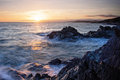 Inspiring and dramatic sea view sunset over the ocean cornwall waves surging rocks uk long exposure Royalty Free Stock Images