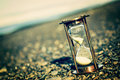 Instagram hourglass sand timer on pebble beach on stony beach with an effect Stock Image