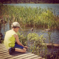 Instagram of young boy feeding ducks from his hand Royalty Free Stock Photo