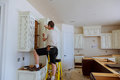 Installation of kitchen. Worker installs doors to kitchen cabinet. Royalty Free Stock Photo