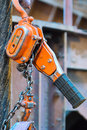 Installed chain hoist a bright orange attached next to a wire rope Stock Photos