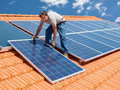 Installing alternative energy photovoltaic solar panels man on roof Stock Images