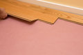 Installing engineered hardwood floor series of shots of being installed by a worker over pink felt paper using hand tools Royalty Free Stock Image