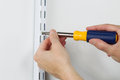 Installing metal bracket on Wall with hand screwdriver Royalty Free Stock Photo