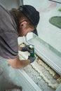 Installing window sill worker installs plastic using polyurethane foam Stock Photos