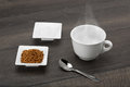 Instant coffee granules and sugar ready for the hot water on dark wooden table Stock Photo