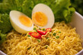 Instant noodles in bowl with vegetables and  boiled egg on wood Royalty Free Stock Photo