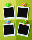 Instant photo frames with heart shape peg four on green background Stock Photo