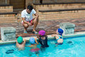 Instructor advising little swimmers at poolside Royalty Free Stock Photo
