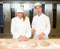 Instructor and baker apprentice kneading bread dough in bakery teaching how to knead Royalty Free Stock Photos