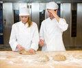 Instructor and baker apprentice kneading bread dough in bakery teaching how to knead Stock Photo