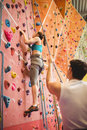 Instructor guiding woman on rock climbing wall women at the gym Royalty Free Stock Photo
