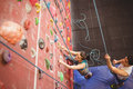 Instructor guiding woman on rock climbing wall women at the gym Stock Images