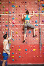 Instructor guiding woman on rock climbing wall women at the gym Royalty Free Stock Image