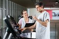 Instructor looking at male client on treadmill happy female drinking water in health center Stock Image