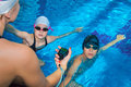 The instructor in the pool with a stopwatch marks the time at th