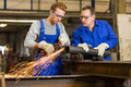 Instructor teaches trainee how to use an angle grinder steel construction Stock Photos