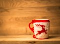 Insulated wool cloth mug with embroidered deer on the wooden table Royalty Free Stock Photo