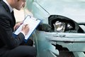 Insurance agent examining car after accident Royalty Free Stock Photo
