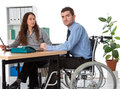 Integration into employment man in wheelchair and his associate on the workplace Stock Photos