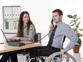 Integration into employment man in wheelchair and his associate on the workplace Stock Images