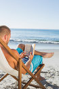 Intellectual handsome man reading a book on the beach Royalty Free Stock Photography