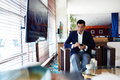 Intelligent man in luxury suit holding his cell telephone while sitting in coffee shop portrait of a confident businessman using Stock Images