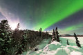 Intense display of northern lights aurora borealis spectacular or or polar forming green swirls and moon behind ice fogs Royalty Free Stock Photos