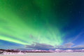 Intense display of northern lights aurora borealis spectacular or or polar forming green swirls over frozen lake laberge Stock Images