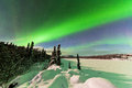 Intense display of northern lights aurora borealis spectacular or or polar forming green swirls over snowy winter landscape Royalty Free Stock Image