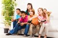 Intense video game with friends group portrait of diversity looking children boys and girls playing videogame sitting on the couch Royalty Free Stock Photo