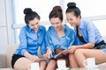 Interesting news portrait of three girlfriends reading indoors Stock Photo