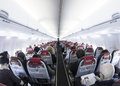 Interior of airplane the an cabin with seats passengers and baggage taken with fisheye lens Stock Photos