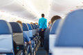 Interior of airplane with stewardess walking the aisle. Royalty Free Stock Photo