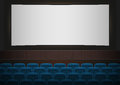 Interior of a cinema movie theatre. Blue cinema or theater seats in front of white blank screen. Empty Cinema auditorium Royalty Free Stock Photo