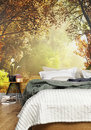 Interior of a cozy Rustic Bedroom with a country nature wall mural background.