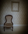 Interior decor background with a vintage chair upholstered standing below an empty wooden picture frame on wallpapered wall Royalty Free Stock Images