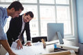 Interior designer discussing blueprint with colleague Royalty Free Stock Photo