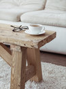 Interior details still life cup of coffee on rustic bench over white sofa Royalty Free Stock Image
