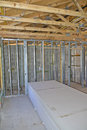 Interior home construction trusses and wood framing in a new house with stack of drywall wall boards Royalty Free Stock Image