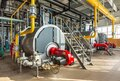 The interior of an industrial boiler room with three large boilers, many pipes, valves and sensors Royalty Free Stock Photo