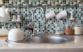 Interior of modern kitchen. Kitchen faucet, sink and various ceramic white dishes Royalty Free Stock Photo