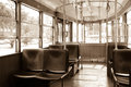 Interior of an old vintage tram. Inside is empty, wooden seats. Shadows. Through the glass windows you can see the trees. sepia. Royalty Free Stock Photo