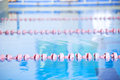 Interior of public indoor swimming pool witch racing lanes and blue water Stock Photos