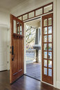 Interior shot of an open wooden front door vertical upscale home with windows Stock Photo