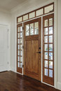 Interior shot of an open wooden front door vertical upscale home with windows Royalty Free Stock Image